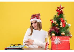 与圣诞节坐在一起的前视女医生在黄色背景上_11819938