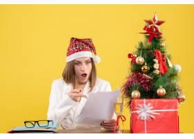 与圣诞节坐在一起的前视女医生在黄色背景上_11820021