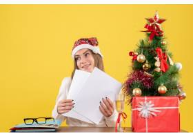 与圣诞节坐在一起的前视女医生在黄色背景上_11819857