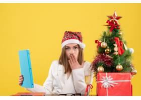 与圣诞节坐在一起的前视女医生在黄色背景上_11819871