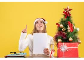 与圣诞节坐在一起的前视女医生在黄色背景上_11819876