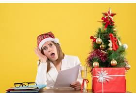 与圣诞节坐在一起的前视女医生在黄色背景上_11819890
