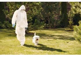 穿着防护服的女人带着狗散步_7368821