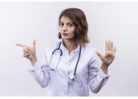 年轻女医生穿着白大褂手持听诊器看着摄_12018238