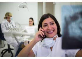 牙医边打手机边看x光报告_8404970