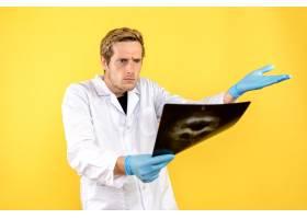 前视男医生在检查头颅X光片背景是浅黄色_11960407