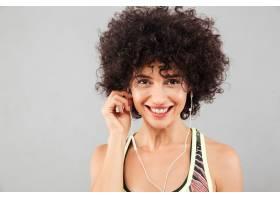 微笑卷曲的健身女子在听音乐的特写图片_7380998