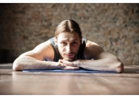 快乐强壮的健身房运动员躺在地板上_8196100