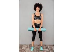 无忧无虑的运动女性手持健身垫子的全长图片_7438355