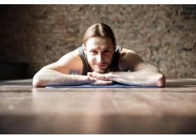 快乐强壮的健身房运动员躺在地板上_8196103