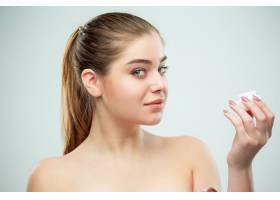 年轻美女在脸上涂抹保湿霜的肖像_6755779