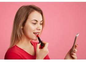 女孩子用红色唇膏画嘴唇用智能手机当镜子_8988316
