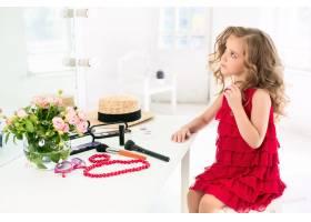 一个带着化妆品的小女孩坐在镜子旁边_7020825