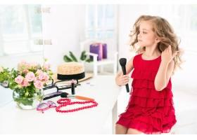 一个带着化妆品的小女孩坐在镜子旁边_7020826