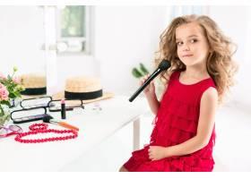 一个带着化妆品的小女孩坐在镜子旁边_7020827