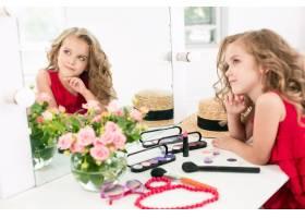 一个带着化妆品的小女孩坐在镜子旁边_7020832