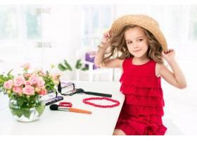 一个带着化妆品的小女孩坐在镜子旁边_7027930