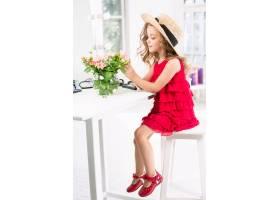一个带着化妆品的小女孩坐在镜子旁边_7027932