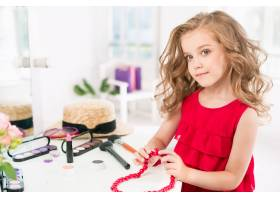 一个带着化妆品的小女孩坐在镜子旁边_7027933