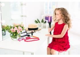 一个穿着红色连衣裙戴着化妆品的小女孩_9405582