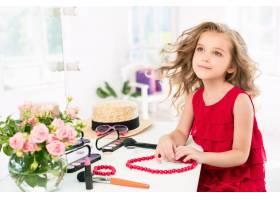 一个穿着红色连衣裙戴着化妆品的小女孩_9405597