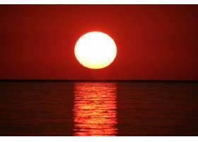 远距离拍摄的海水用红色的天空反射太阳_805472801