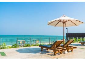 酒店和度假村游泳池周围有漂亮的伞和椅子_409805501