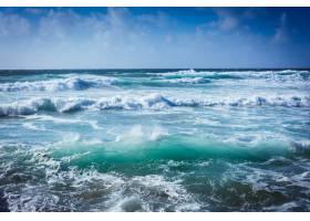 阳光和蓝天下波涛汹涌的大海的景观_1167806701