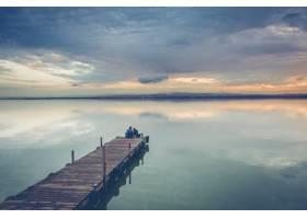 美丽的一对夫妇坐在美丽的日落天空下的木质_1285933901