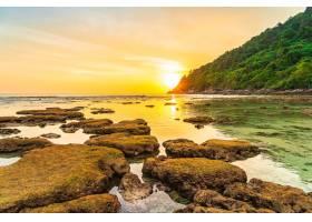 美丽的日落在海滩大海和岩石周围的山上落_1120618001