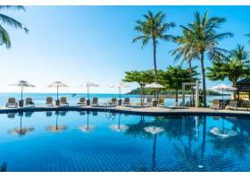 美丽的热带海滩和大海游泳池周围有伞和椅_353187701