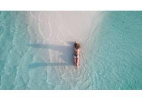 航拍到一个女孩躺在沙滩上晒黑_781044001