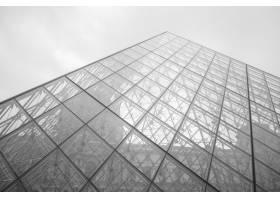 法国巴黎多云天空下的卢浮宫的灰度照片_999153601