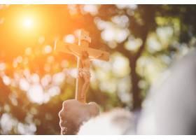 手持木头耶稣的男子手持自然背景穿越天空_118602001