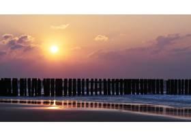 海滩上紫云缭绕的日落美景_1290971201
