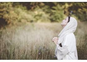 浅聚焦镜头女性身穿圣经长袍头朝天祈祷_1075885101