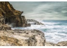 海浪在多云的灰色天空中撞击着海岸上的岩石_1118381801