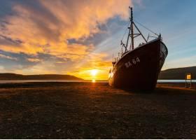 日出时一艘渔船接近海滩的美丽镜头_767804601