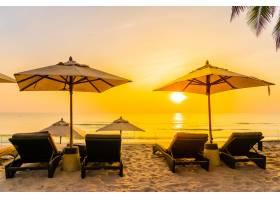 日出时分在美丽的海滩和大海上放雨伞和椅子_432096001