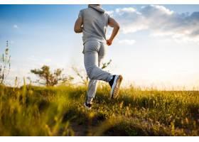 日出时分运动型男子在田野慢跑的特写镜头_785112701