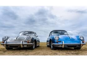 灰色和蓝色的汽车在多云的天空下并排放在一_1041974101