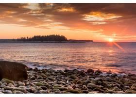 多石的海边背景是夕阳的美丽镜头_828091001