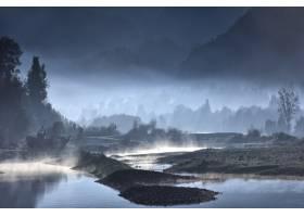 夜晚有森林的雾蒙蒙的湖岸_1054274001