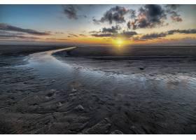 多云天空下泥滩上倒映的夕阳美景_1230540201