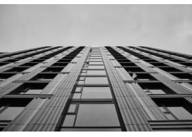 多云天空下现代摩天大楼的灰度_1041958401