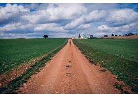 多云天空下绿色草地上的狭窄小路_1285929601