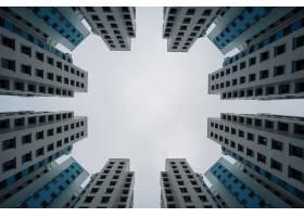 多云天空下蓝白相间的现代建筑的低角视角_1106269301