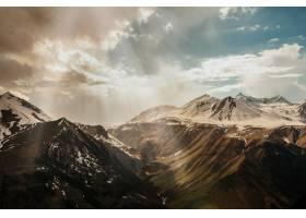 太阳光穿过云层到达白雪皑皑的高山山脉_245490001