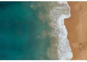 从空中俯瞰美丽的海浪与海滩上的沙子相遇_885762501