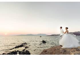 从远处看可爱的新婚夫妇看着海面上的日落_398499801